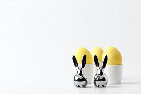 yellow painted easter eggs in egg stands and statuettes of rabbits on white